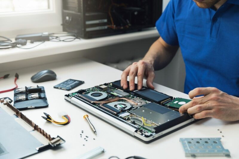 computer repairman installing new hard disk drive in laptop